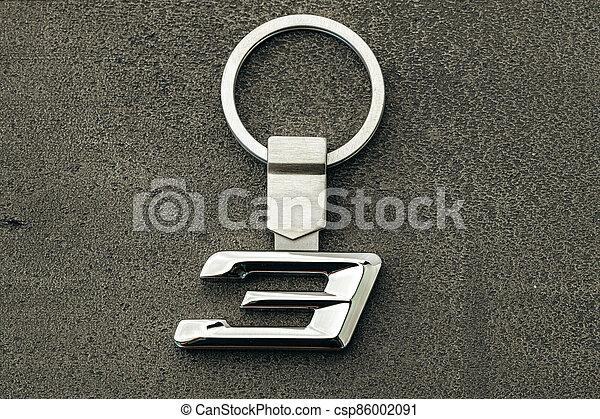 Metal number Three car key on dark concrete background - csp86002091