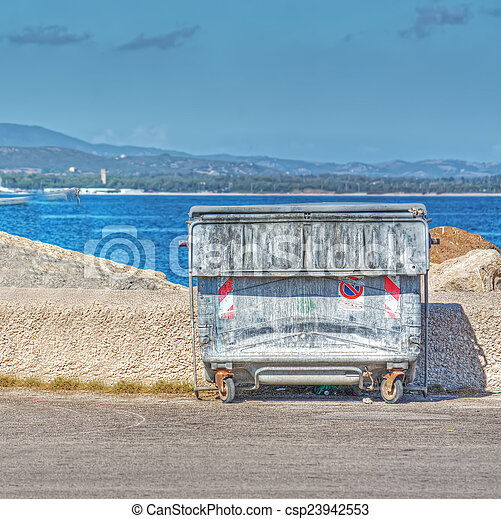 Un contenedor de basura de metal en la orilla - csp23942553