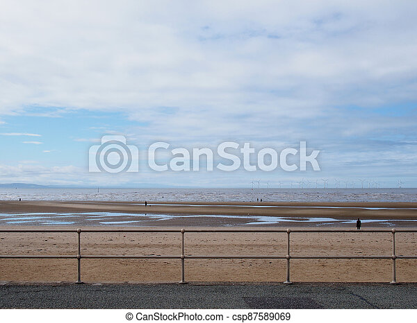 metal railings on the seafront in crosby near southport with a dog on the beach under a blue cloudy sky - csp87589069