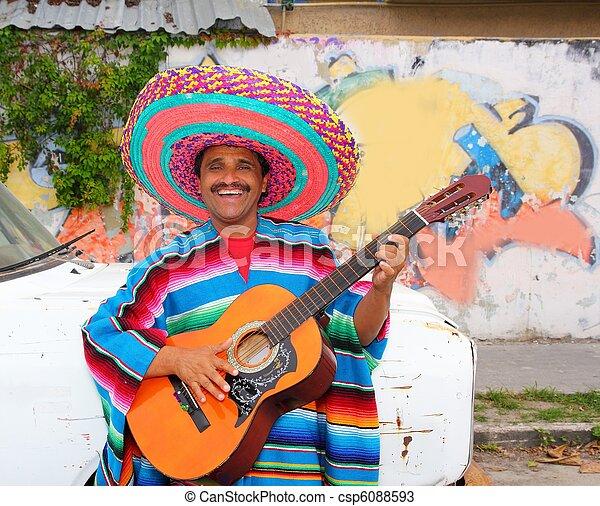 Mexican humor man smiling playing guitar sombrero - csp6088593