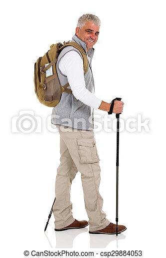 mid age man walking with trekking poles - csp29884053