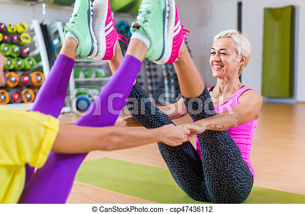 midaged woman working out in pairs on mats in a gym in