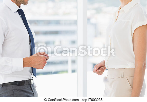 Mid section of executives exchanging business card - csp17603235
