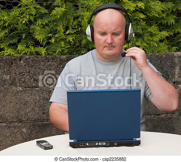 middle age man using laptop and voip  - csp2235882