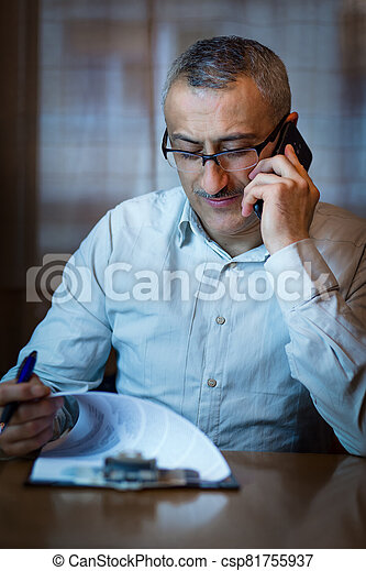 Middle age manager speaking over the phone, checking reports, papers. - csp81755937