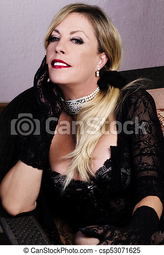 Middle-Aged Blond Caucasian Woman Sitting In Black Lacy Lingerie - csp53071625