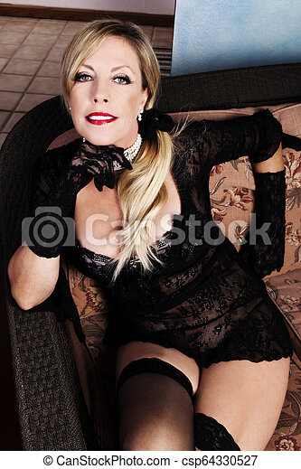 Middle-Aged Caucasian Woman Sitting In Black Lacy Lingerie - csp64330527