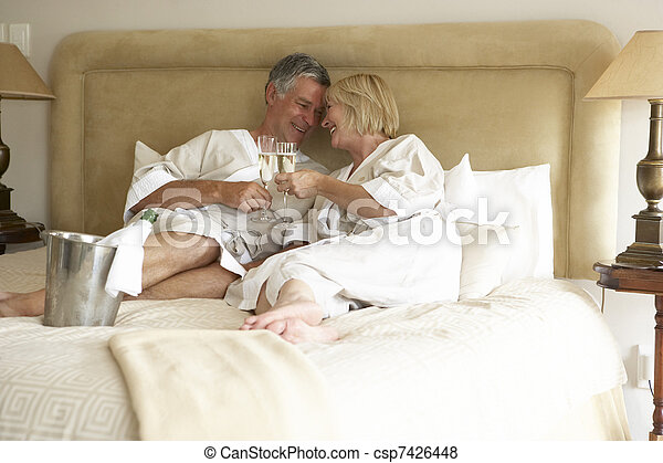 Middle Aged Couple Enjoying Champagne In Bedroom - csp7426448