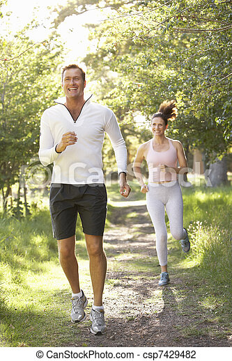 Middle Aged Couple Jogging In Park - csp7429482