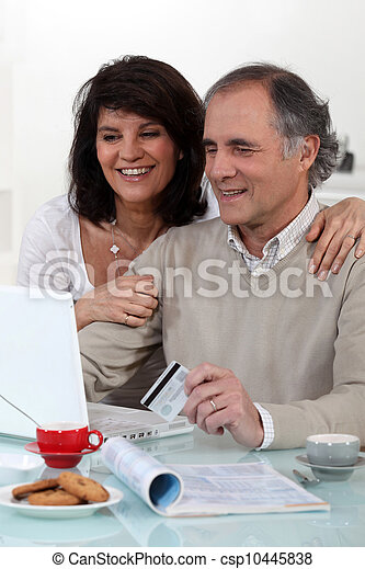 Middle-aged couple sat at computer with credit-card - csp10445838