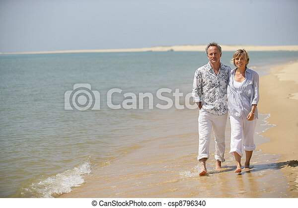 Middle-aged couple strolling along the shore - csp8796340