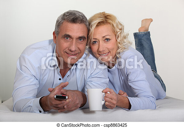 Middle-aged couple watching television - csp8863425