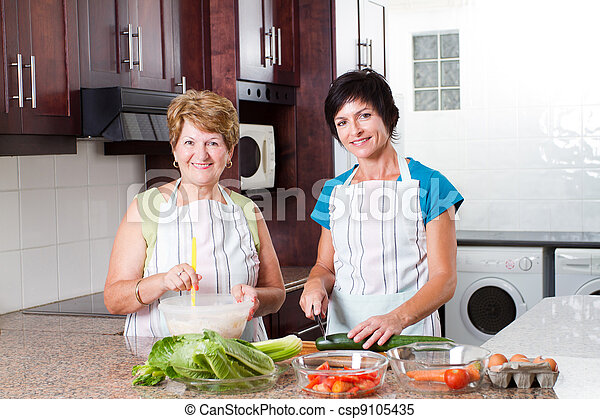 middle aged woman cooking with senior mother - csp9105435