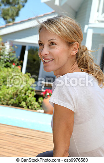 Middle-aged woman doing fitness exercises outside - csp9976580
