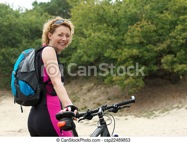 Middle aged woman smiling with bike - csp22489853