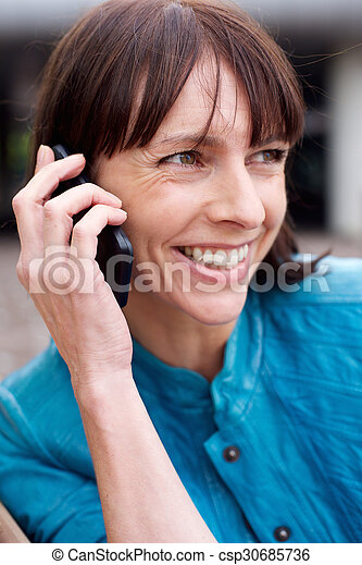 Middle aged woman smiling with mobile phone - csp30685736