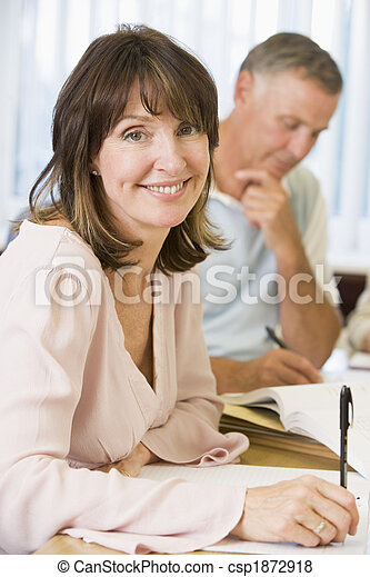 Middle aged woman studying with other adult students - csp1872918