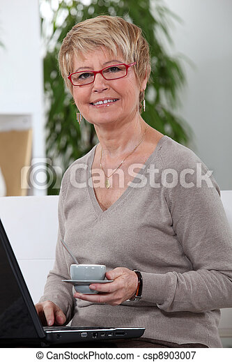 Middle-aged women drinking coffee whilst surfing the internet - csp8903007