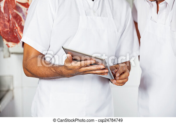 Midsection Of Butchers Using Digital Tablet - csp24784749