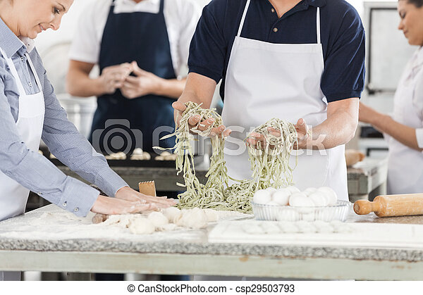 Midsection Of Chefs Preparing Pasta In Kitchen - csp29503793