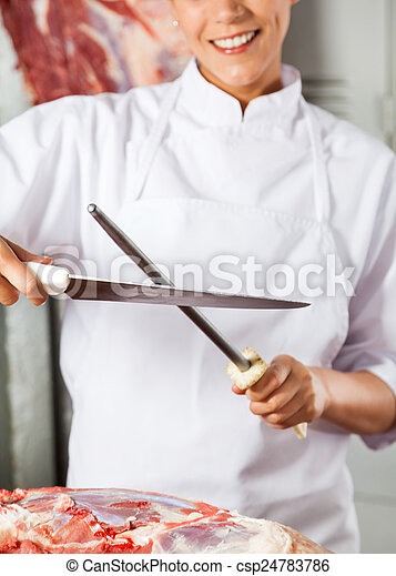 Midsection Of Female Butcher Sharpening Knife - csp24783786