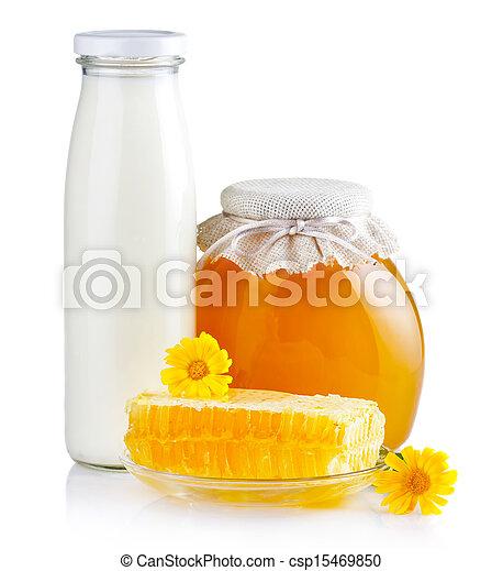 Dulce miel en tarros de cristal con flores, panales y leche en blanco - csp15469850
