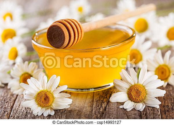 Un tazón de miel con flores de margarita - csp14993127