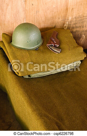 Military bed with helmet and pistol - csp6226798