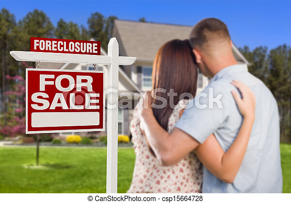Military Couple Standing in Front of Foreclosure Sign and House - csp15664728