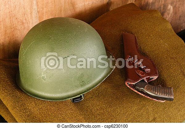 Military helmet and revolver on blanket - csp6230100