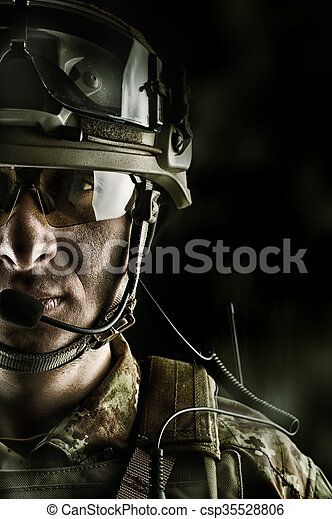 military man in camouflage wearing helmet, glasses, radio set - csp35528806