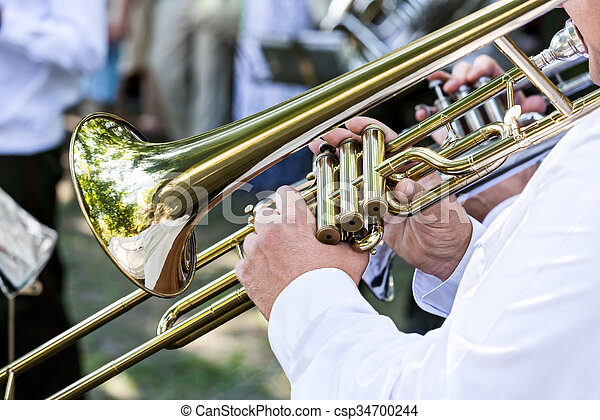 military musician blowing his gold trombone - csp34700244