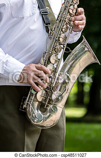 military orchestra musician playing saxophone on music festival - csp48511027