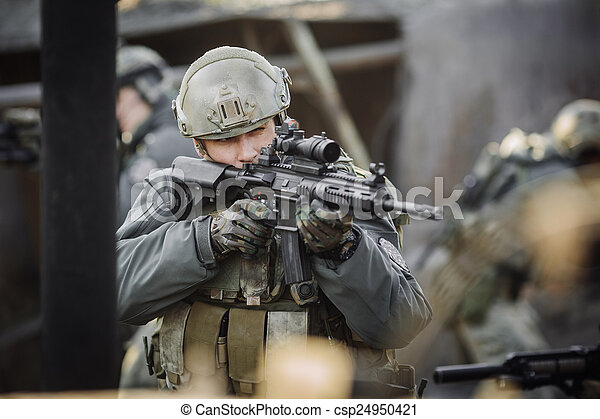 military soldier shooting an assault rifle - csp24950421