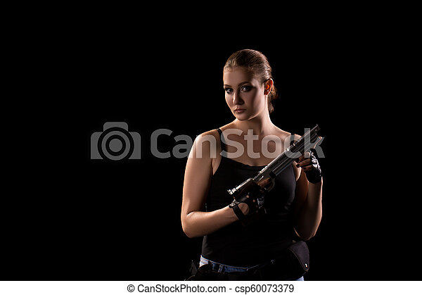 Military woman with a gun over black background - csp60073379
