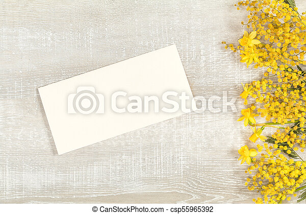 Mimosa and yellow daffodils on a light wooden surface - csp55965392