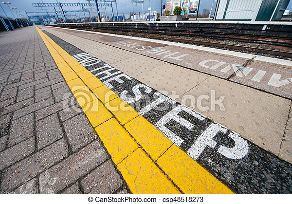 Mind the step yellow text line in British train station - csp48518273
