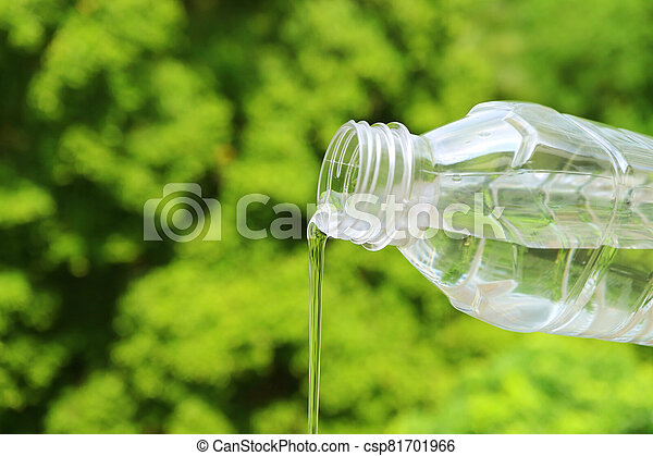 Mineral water flowing from plastic bottle with blurry green foliage in background - csp81701966