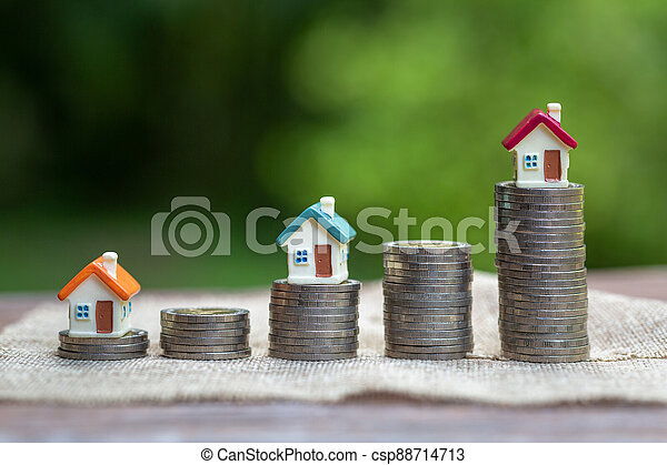 Mini house standing on a heap of coins. The concept of purchase of habitation. - csp88714713