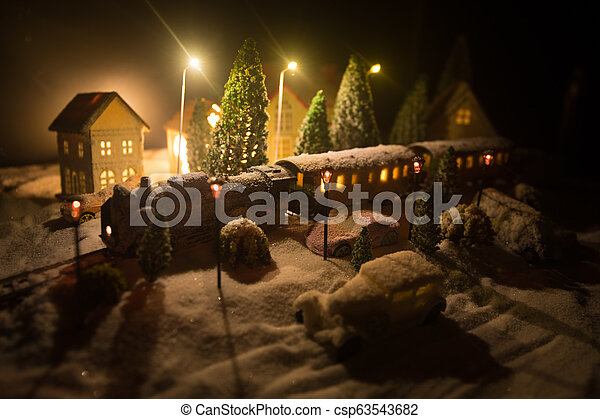 Miniature of winter scene with Christmas houses, train station, trees, covered in snow. Nights scene. New year or Christmas concept. - csp63543682
