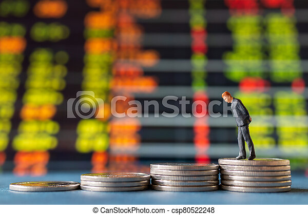 Miniature people , Businessman standing on stack of Coins with graph display background - csp80522248
