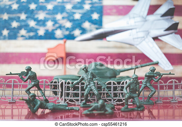 Miniature toy soldiers in battle scene with american flag background - csp55461216