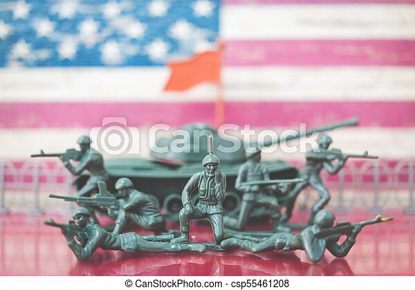Miniature toy soldiers in battle scene with american flag background - csp55461208