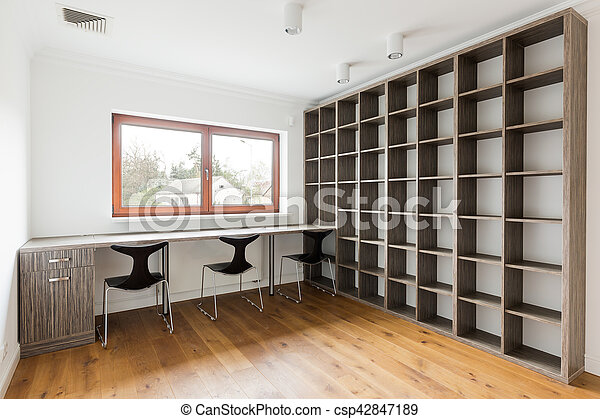 Minimalist Empty Office With A Long Desk And Large Bookshelf