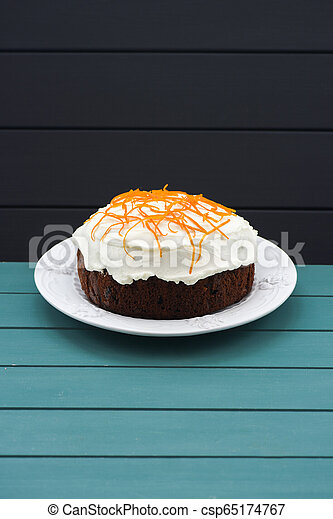 Minimalist style pastry. Homemade traditional fruit cake with cream icing and orange peel on blue background copyspace - csp65174767