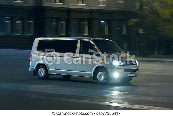 Minivan moves at night on a city street - csp77385417