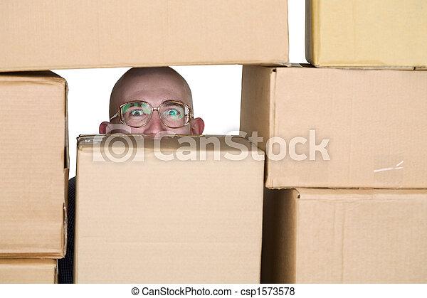 Un hombre mirando a través de cajas de cartón - csp1573578