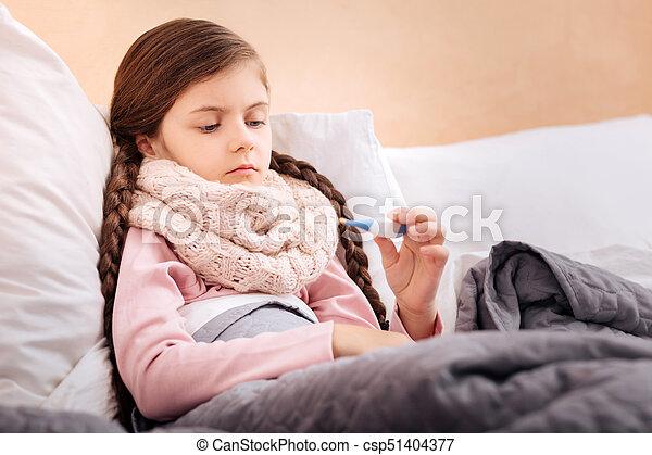 Un niño enfermo mirando atentamente el termómetro - csp51404377