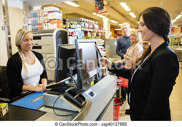 La cajera está mirando a una clienta haciendo el pago de la NFC - csp40137885