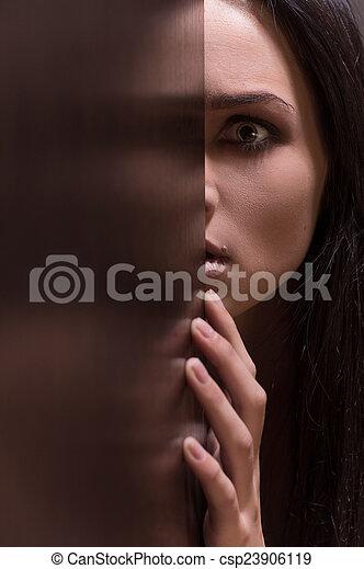 Hermosa joven morena, luciendo asustada. Miedo en la cara femenina con media cara en la entrada - csp23906119